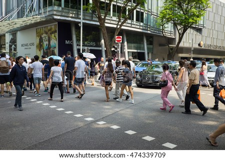 Singapore - May 1 2016: People crossing street in Orchard Rd, Singapore