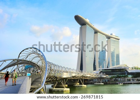 SINGAPORE - MAY 03, 2013 : The Helix Bridge and Marina Bay Sands in Singapore. Marina Bay is billed as the world's most expensive standalone casino property at S$8 billion  - stock photo