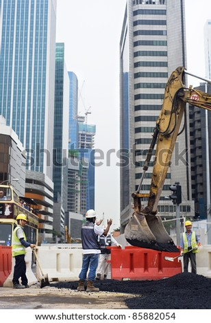 SINGAPORE - MAY 2: Workers repair roads on the one of Singapore street on May 2, 2011 in Singapore. Construction industry is expected to pull in some S$30 billion this year - stock photo