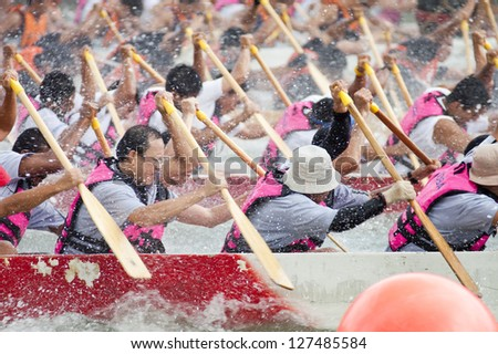 SINGAPORE- NOVEMBER 21: Teams of men in Dragon boats paddle vigorously in a  race in the downtown area of Singapore on November 21, 2004. Dragon Boat Racing is a popular team sport in Singapore.