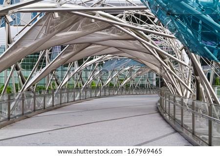 SINGAPORE - NOVEMBER 14: The Helix Bridge on November 14, 2013 in Singapore. Is a pedestrian bridge linking Marina Centre with Marina South in the Marina Bay. - stock photo