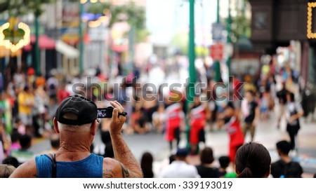 SINGAPORE- NOVEMBER 9, 2015: Tourists Taking Video of a Show/Performance at Universal Studios in Singapore. Universal Studios is an American Film Studio that is also famous in Theme Park Business. - stock photo