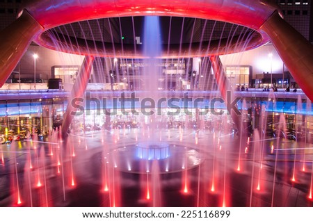 SINGAPORE-OCT 11: Fountain of Wealth with Suntec Towers at dusk on OCT 11,2014 in Singapore. Fountain of wealth is the biggest fountain in Singapore located Suntec Towers, SINGAPORE. - stock photo