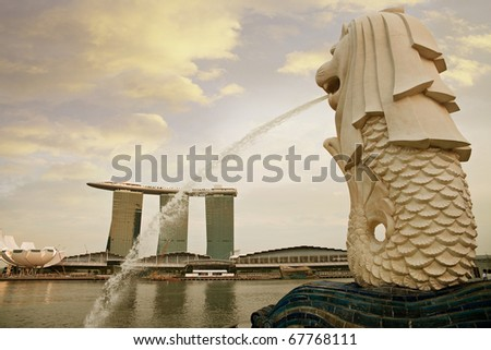 SINGAPORE - OCT 14: Merlion, Singapore's national symbol looking through Marina Bay at evening time on Oct 14 ,2010 in Singapore. - stock photo