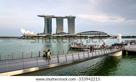 SINGAPORE â?? OCT 29, 2015: Visitors at Merlion Park fountain. Merlion is an imaginary creature with half lion, half fish, seen as a symbol of Singapore. ArtScience Museum and Marina Bay Sands - stock photo