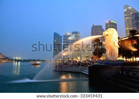SINGAPORE - OCTOBER 24,2015: Financial district skyscrapers and Merlion at Marina bay. The Merlion is a traditional creature with a lion head and a body of a fish, seen as a symbol of Singapore. - stock photo