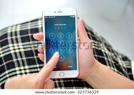 SINGAPORE - OCTOBER 4, 2015: Woman holding Apple iPhone 6S plus. Social media are trending and both business as consumer are using it for information sharing and networking. - stock photo