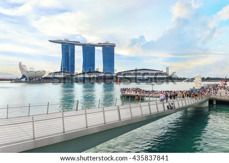 Singapore, Republic of Singapore - May 7, 2016: Crowds of tourists admire the view of Marina Bay Sands hotel, ArtScience museum and Flyer near Merlion sculpture
