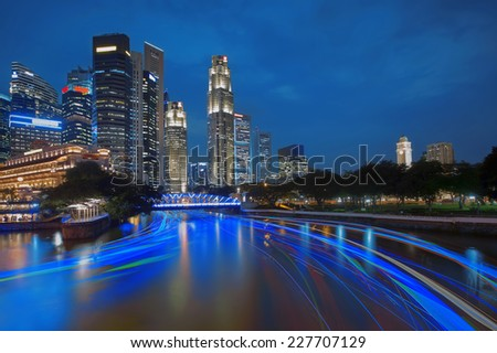Singapore river cruise and skyscrapers at sunset - stock photo