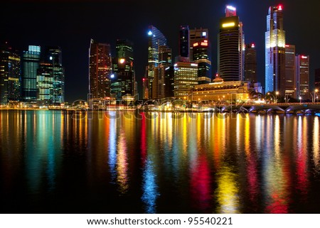 Singapore's downtown skyscrapers reflected on water at night - stock photo