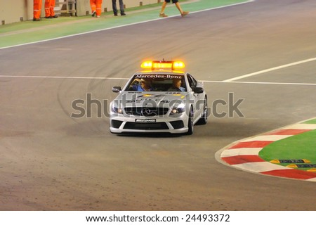 SINGAPORE - SEPTEMBER 26: Formula One safety car approaching corner during first night race September 26, 2008 in Singapore - stock photo