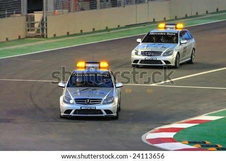 SINGAPORE - SEPTEMBER 26: Medical cars driving around circuit during first Formula One night race September 26, 2008 in Singapore - stock photo