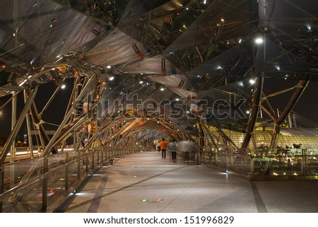 SINGAPORE - SEPTEMBER 04: The Helix Bridge and Marina Bay Sands on September 04, 2012 in Singapore. The Helix is fabricated from 650 tonnes of Duplex Stainless Steel and 1000 tonnes of carbon steel. - stock photo