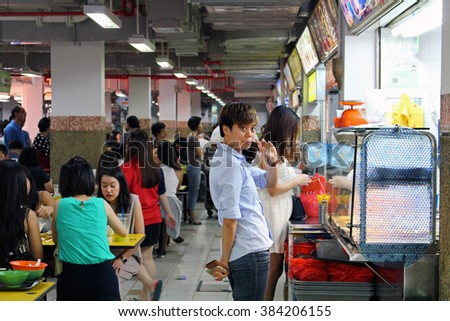SINGAPORE/SINGAPORE - CIRCA NOVEMBER 2015: People queueing for a meal in  a stall in a singaporean hawkers center - stock photo