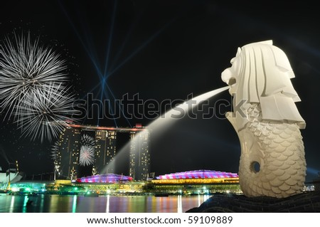 Singapore skyline and river shining with fireworks at night