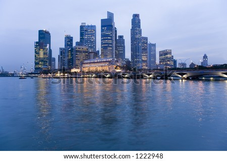 Singapore skyline reflected in the water of the harbour at dusk or twilight