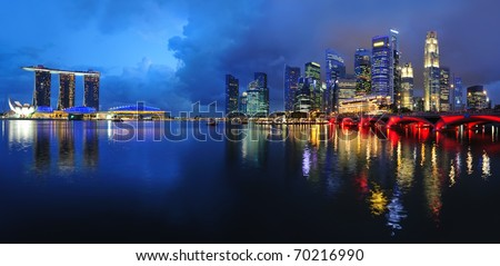 Singapore waterfront cityscape skyline with reflections in the dark blue water. - stock photo