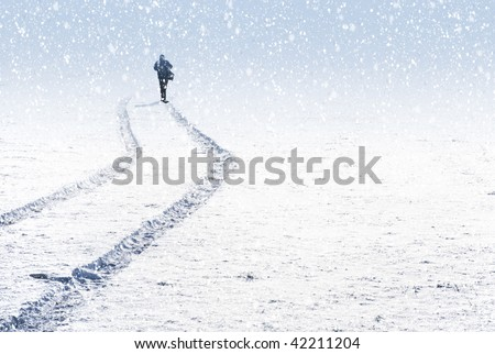Singe person silhouette through snow and car trails on snow. - stock photo