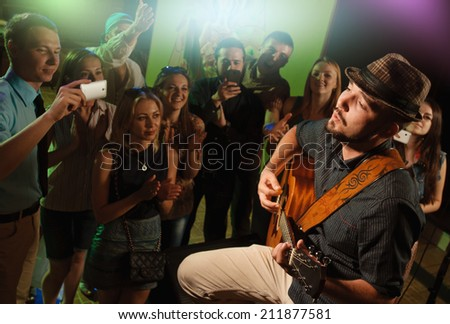 singer and guitarist performing on stage in a club in front of a cheering crowd