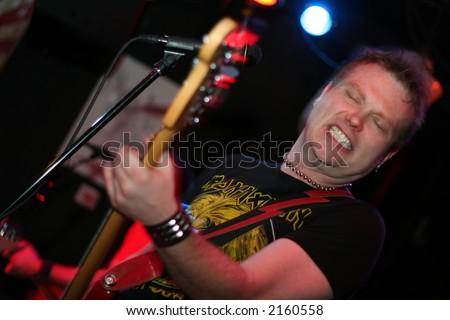 Singer playing guitar and rocking out (slight motion blur) - stock photo