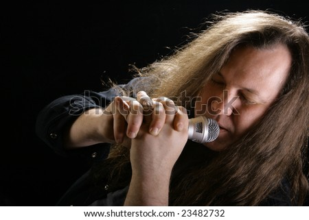 Singer with microphone over black background - stock photo