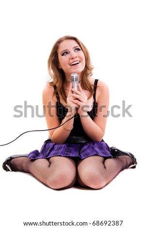 Singer. Young girl singing into microphone. - stock photo