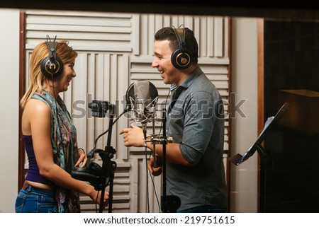 Singers laughing while recording a song in the studio - stock photo