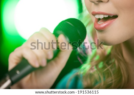 Singing Girl. Blond karaoke girl singing - stock photo