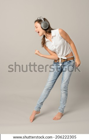 Singing girl with headphones enjoy dance full length gray background - stock photo