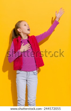 Singing girl. Young blond singing with arm raised. Three quarter length studio shot on yellow background. - stock photo