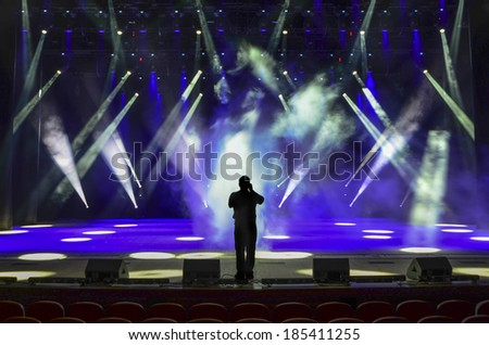 singing man silhouette on a brightly lit concert stage - stock photo