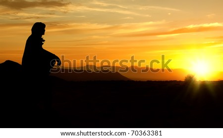 single adult woman silhouette on rock watching yellow and orange setting sun in distance - stock photo