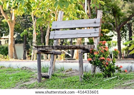 single aged wooden bench on the lawn near pathway in the park, outdoor place for relaxation - stock photo
