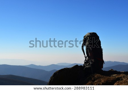 single backpack on the mountains panorama - stock photo