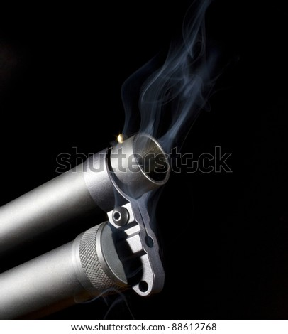 Single barreled shotgun with a black background with the muzzle smoking - stock photo