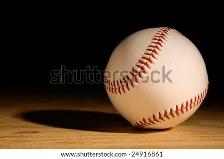 single baseball on wood plank coming out of the shadows
