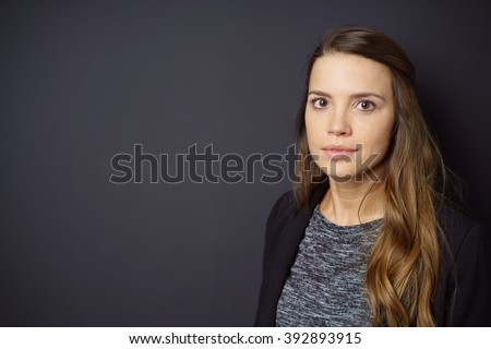 Single beautiful calm woman in gray sweater and long brown hair in front of dark background with copy space