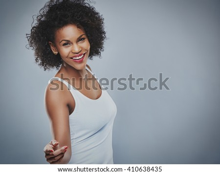 Single beautiful carefree and happy woman dancing over gray background with copy space to side