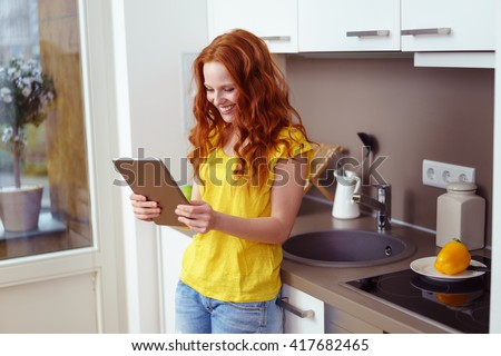 Single beautiful young female with long red hair looking at her tablet computer while leaning against kitchen sink counter - stock photo