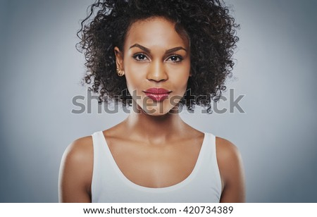 Single beautiful young upbeat grinning woman in soft frizzy hair and bare shoulders over gray background - stock photo