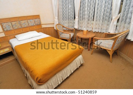 Single bed neatly done up in a high class hotel room with table and chairs. Suitable for concepts such as travel, tourism, vacation and holiday. - stock photo