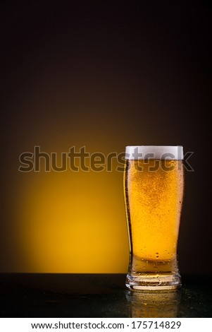 Single beer glass against vivid orange background - stock photo