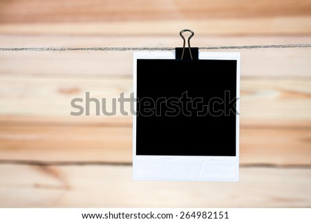 Single black instant photo, hanging on the clothesline on wooden background. - stock photo