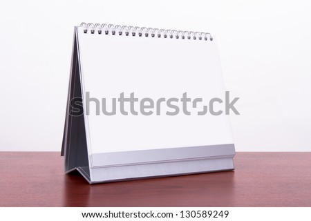 Single blank desk calendar on wooden table, isolated on white background. - stock photo