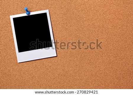Single blank polaroid photo print, pushpin, cork board.  Copy space - stock photo