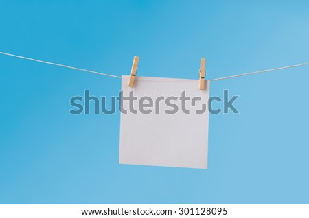 Single, blank square of white paper, suspended from a washing line by two wooden pegs.  Left blank to provide copy space. - stock photo