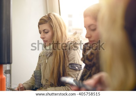 Single blond woman in gray winter coat sitting inside crowded commuter train or bus in front of window - stock photo