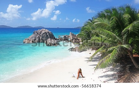 Single Blonde Sun worshiper with Beach all to herself in The Seychelles - stock photo