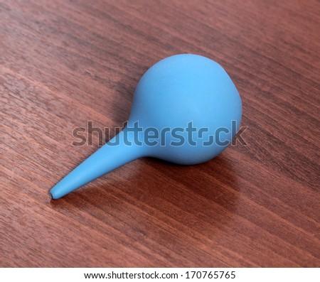 Single blue medical enema on wooden background - stock photo