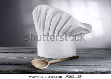 single blue table with one wooden spoon and cook cap
